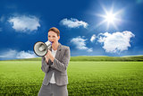 Composite image of businesswoman talking on a megaphone