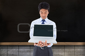 Composite image of businessman showing a laptop