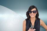 Composite image of happy brunette holding smartphone