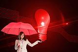 Composite image of happy businesswoman holding umbrella