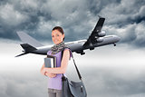 Composite image of attractive student holding books and her bag while standing