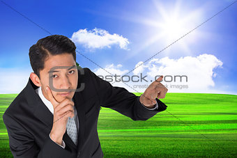 Composite image of thoughtful asian businessman pointing
