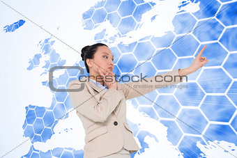 Composite image of thoughtful asian businesswoman pointing