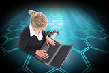 Composite image of businesswoman using laptop