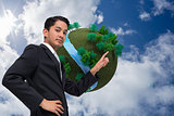 Composite image of unsmiling asian businessman pointing