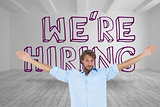 Handsome man raising arms in front of were hiring graphic
