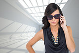Composite image of serious elegant brunette wearing sunglasses on the phone