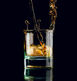 Glass of whiskey on a black background.