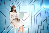 Composite image of smiling businesswoman sitting and using laptop