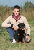 man and puppy rottweiler