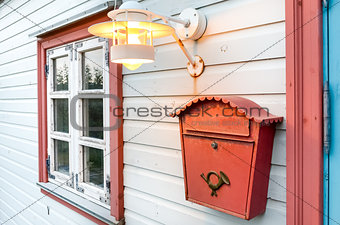 Mail box, window and lamp on a white wooden house