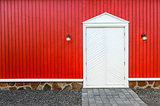 Red wooden wall and white front doors with two lamps