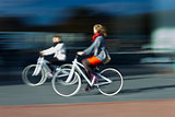 two women on the blurred bikes in profile