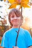 Portrait of a Boy Holding a Brown Leaf
