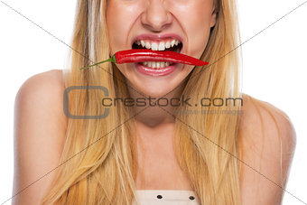 Closeup on teenage girl holding red chili pepper in mouth