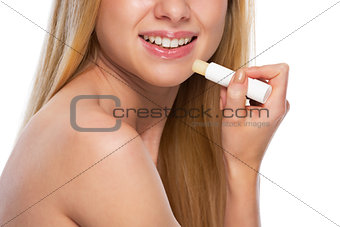 Closeup on happy teenage girl applying hygienic lipstick