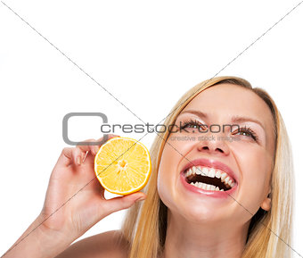 Portrait of teenage girl holding lemon and looking on copy space