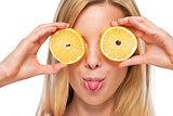 Portrait of happy teenage girl holding lemon in front of eyes