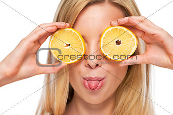 Portrait of happy teenage girl holding lemon in front of eyes
