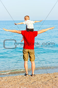 Father and son on the beach portraying flight
