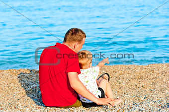 son and father sitting by sea