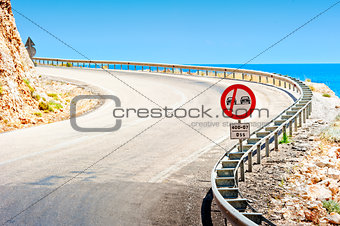 road sign and a mountain road along the sea
