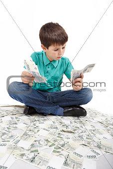boy sitting on money, money concept