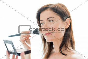 attractive woman in her forties applying makeup to her face
