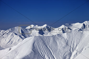 Off-piste slope with traces of skis and snowboards in nice day