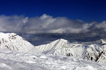 Ski slope and beautiful snowy mountains in clouds.