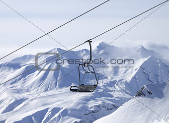 Chair lifts and off-piste slope in fog