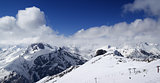 Panoramic view on ski slope and cloudy mountains at nice sun day