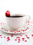 White cup of coffee decorated with red heart