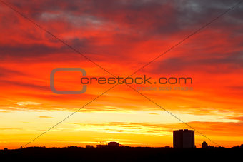 bright red, yellow, blue clouds in sunrise sky