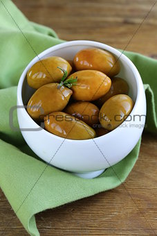 green marinated olives in a white bowl
