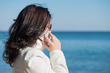Woman is speaking by mobile phone at the seaside