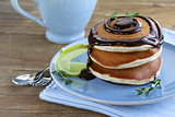 homemade pancakes with chocolate syrup and thyme