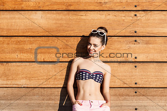 beautiful sexy girl poses against wooden wall