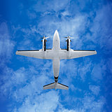 Bottom view - twin prop airplane on sky background