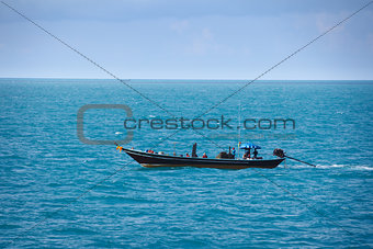 Old fishing boat goes by sea - fishermen working