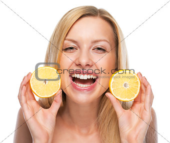 Portrait of happy teenage girl showing lemon slices