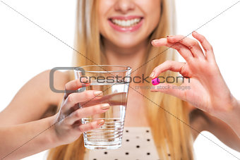 Closeup on smiling teenage girl giving cup of water and pill