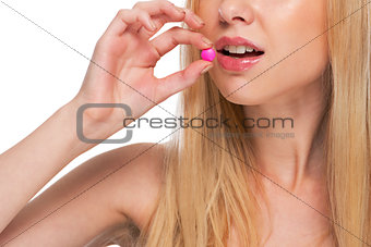 Closeup on teenage girl eating pill