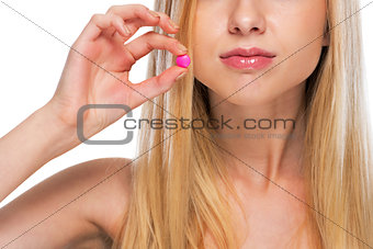 Closeup on teenage girl showing pill