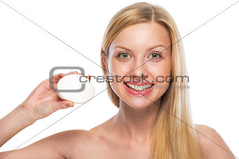Portrait of smiling teenage girl showing soap bar