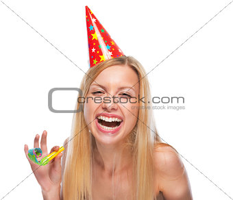 Portrait of happy teenage girl in cap with party horn blower