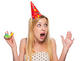 Portrait of surprised teenage girl in cap with party horn blower