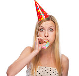 Portrait of teenage girl in cap blowing in party horn blower