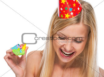 Portrait of smiling teenage girl in cap with party horn blower