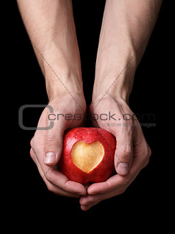 adult man hands holding apple with carved heart